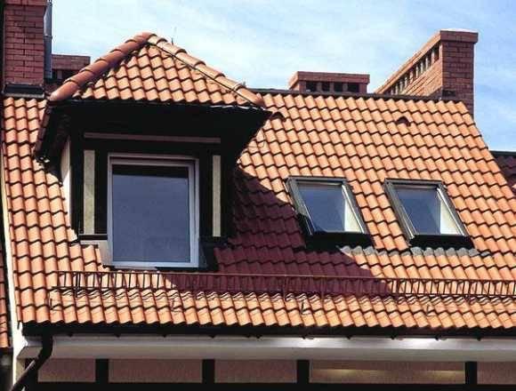 Слуховое и мансардные окна на крыше загородного дома