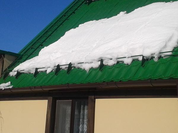 Работа снегозадержателей установленных на крыше дома