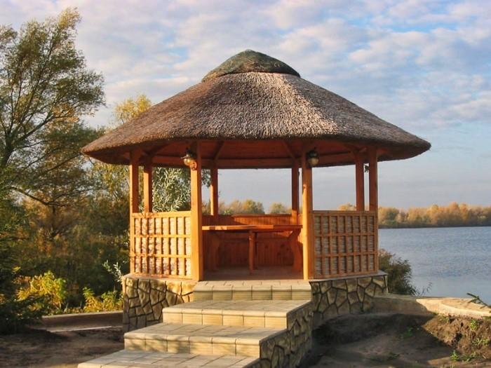 Беседка на берегу реки с соломенной крышей